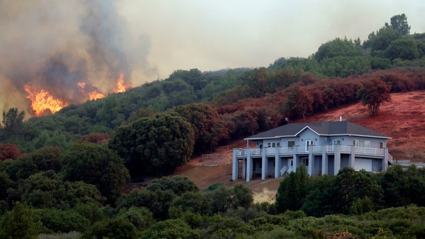 A wildfire crests over a ridge, threatening a home, bottom right, Monday, July 30, 2018, in Lakeport, Calif.