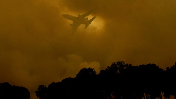 An air tanker passes behind a smoke plume while battling the River Fire in Lakeport, Calif., on Monday, July 30, 2018.