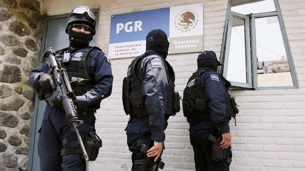 """May 19: Federal police stand guard outside the Attorney General's office (PGR) in Cuernavaca after the arrest of Victor Valdez, known as """"El Gordo Varilla"""" (The Big Stick)."""