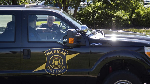 Michigan State Police talk outside Bishop International Airport, Wednesday morning, June 21, 2017, in Flint, Mich.