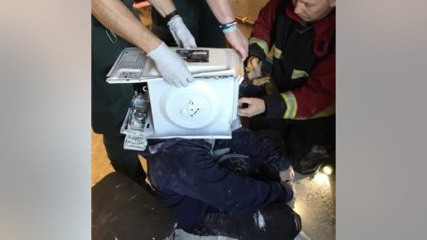 Firefighters were called to rescue a man who had cemented a microwave oven on his head in a YouTube stunt. (© West Midlands Fire Service)