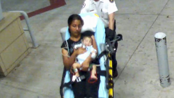 Surveillance footage shows a woman and a 2-month-old boy entering Oklahoma City hospital. Infant later disappeared and was found in Dallas. (Oklahoma City Police Department)