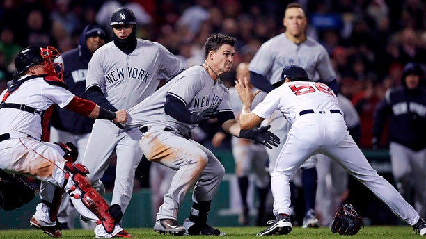 New York Yankees' Tyler Austin, center, rushes Boston Red Sox relief pitcher Joe Kelly, right, after being hit by a pitch during the seventh inning of a baseball game at Fenway Park in Boston.