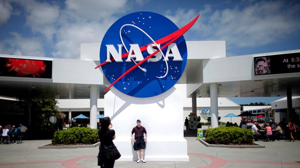 File photo: Tourists take pictures of a NASA sign at the Kennedy Space Center visitors complex in Cape Canaveral, Florida April 14, 2010. (REUTERS/Carlos Barria)