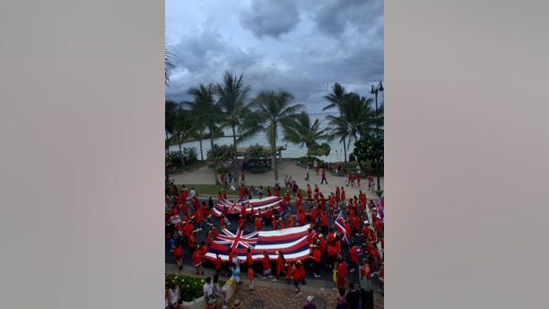 """Thousands of native hawaiians and local supporters wearing red shirts carry large Hawaii state flags overflowed Kalakaua Avenue as they marched along side Waikiki Beach in Honolulu, Hawaii, Sept. 6, 2004. Hawaiian clubs, trusts, agencies and schools, marshal over 5,000 to protest threats to native Hawaiian entitlements and land trusts as well as U.S. military expansion on the islands. For the second year in a row, trustees and representatives from alii trusts, state and civic organizations, and native and non-Hawaiian supporters joined together in a march for """"Ku I Ka Pono,"""" or """"justice for Hawaiians."""" (REUTERS/Lucy Pemoni)"""