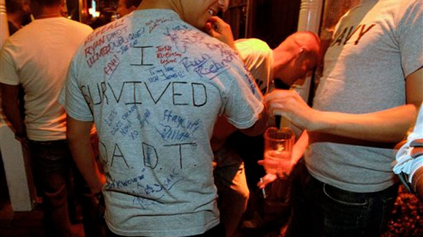 A man who is active-duty in the Navy wears a shirt being signed by others that reads 'I survived D.A.D.T.' shortly before midnight during a celebration for the end of the policy Sept. 19 in a bar in San Diego.