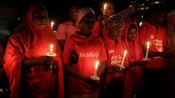 April 14, 2015: People hold candles during a vigil to mark the one year anniversary of the abduction of girls studying at the Chibok government secondary school, Abuja, Nigeria.