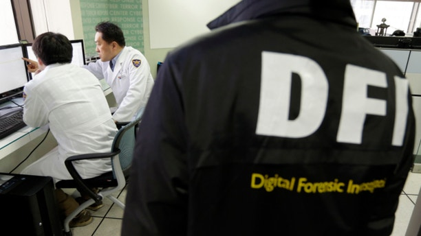 March 21, 2013: South Korean computer researchers, left, check the computer servers of Korean Broadcasting System (KBS) as a South Korean police officer from Digital Forensic Investigation watches at the Cyber Terror Response Center at the National Police Agency in Seoul, South Korea.
