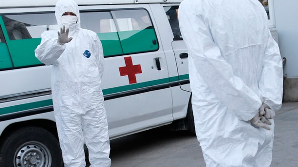 Oct. 27, 2014: This photo shows medical personnel in protective suits standing by an ambulance, at the Sunan International Airport, in Pyongyang, North Korea.