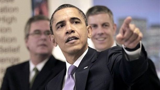 President Obama points as he tours classrooms at Miami Central Senior High School with Education Secretary Arne Duncan, right, and former Florida Gov. Jeb Bush March 4 in Miami.