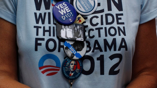 A supporter of Obama wears a collection of badges in the audience during a 2012 election campaign rally in Colorado Springs.