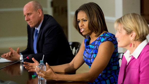 May 27, 2014: This photo shows first lady Michelle Obama, with Eric Goldstein, chief executive officer, Office of School Support Services, New York City Department of Education, left, and Donna Martin, School Nutrition Program, Burke County Board of Education, in Georgia, during a discussion with school leaders and experts on school nutrition in an event in the Eisenhower Executive Office Building on the White House complex in Washington. (AP)