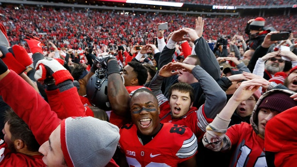 FILE - In this Saturday, Nov. 26, 2016, file photo, Ohio State players and fans celebrate their win over Michigan in an NCAA college football game in Columbus, Ohio.
