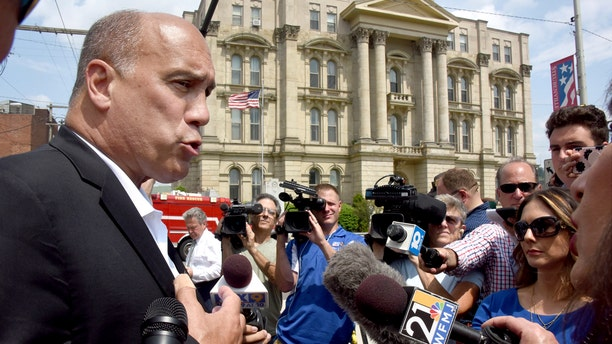 City of Steubenville manager Jim Mavronatis talks to the media with the Jefferson County Courthouse in the background.