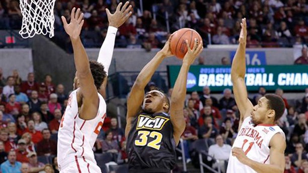 VCU guard Melvin Johnson, center, goes up for a basket between Oklahoma guard Buddy Hield, left, and Oklahoma guard Isaiah Cousins, right, in the first half of a second-round men's college basketball game in the NCAA Tournament in Oklahoma City, Sunday, March 20, 2016. Oklahoma won 85-81. (AP Photo/Alonzo Adams)