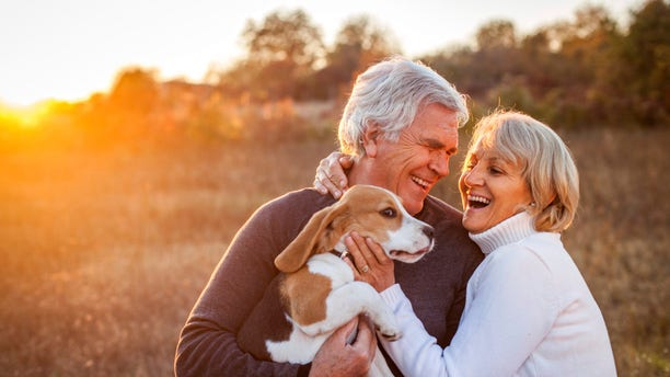 An older boomer couple enjoy time with their dog.