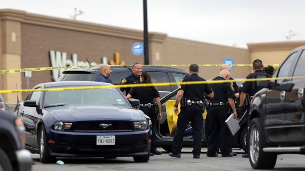 San Antonio police investigate the scene of a shooting in the Wal-Mart parking lot in San Antonio, Friday, Nov. 25, 2016.