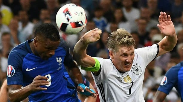 Germany's midfielder Bastian Schweinsteiger (R) touches the ball with his hand as he jumps with France's defender Patrice Evra (L), leading to a penalty for France, during the Euro 2016 semi-final football match between Germany and France at the Stade Velodrome in Marseille on July 7, 2016. / AFP / ANNE-CHRISTINE POUJOULAT (Photo credit should read ANNE-CHRISTINE POUJOULAT/AFP/Getty Images)