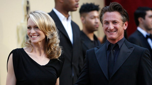 "Best actor nominee Sean Penn from the film ""Milk"" and his wife Robin Wright Penn pause on the red carpet as they arrive at the 81st Academy Awards in Hollywood, California February 22, 2009. Sean Penn is dressed in Giorgio Armani and Robin Wright Penn, dressed in Monique Lhuillier. REUTERS/Mario Anzuoni   (UNITED STATES) (OSCARS-ARRIVALS) - GM1E52N0PKZ01"
