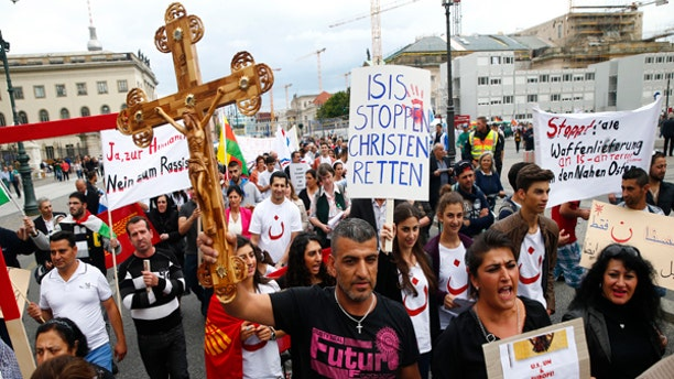 """August 17, 2014: People hold crosses and signs during a rally organized by Iraqi Christians living in Germany denouncing what they say is repression by the Islamic State militant group against Christians living in Iraq, in Berlin. Some of the signs read """"Stop ISIS, save the Christians"""" and """"Stop all shipment of weapons into the Middle East."""""""