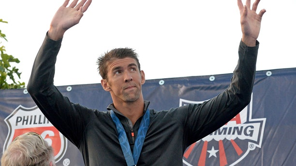 FILE 2014: Michael Phelps on the podium after getting his second place medal for the Men's 100 Meter Butterfly final at the USA Swimming Nationals at the William Woollett Jr. Aquatics Complex.