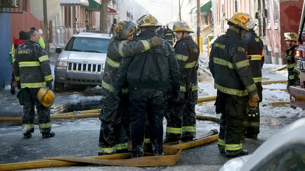 Firefighters embrace after putting out the deadly blaze on North Colorado Street in North Philadelphia.