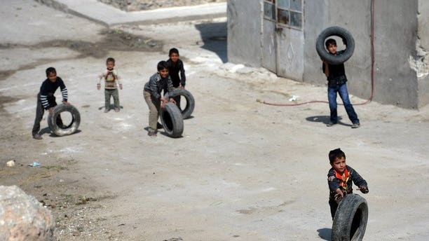 Syrian children roll used car tyres on a street in the northern Syrian city of Aleppo on April 12, 2013. An epidemic of measles is sweeping through parts of northern Syria, with at least 7,000 people affected because the ongoing civil war has disrupted vaccination programmes, Doctors Without Borders said on Tuesday.
