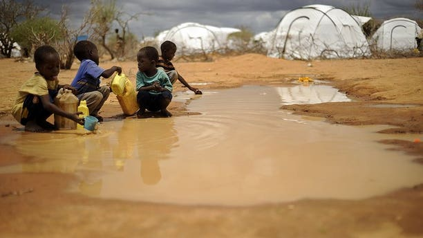 Boys fetch water from a puddle at a refugee complex in Kenya, on October 16, 2011. At least 10 people were killed in a grenade attack on a displaced people's camp in the far northeastern tip of Kenya near the borders with Somalia and Ethiopia, police said.