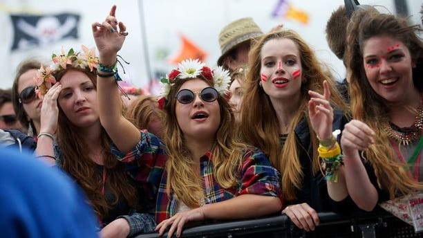 Festival goers attend concerts at the Pyramid Stage during the third day of the Glastonbury Festival, southwest England, on June 28, 2013. The sun was out the world-renowned festival, drying the mud underfoot as tens of thousands waited for the first ever performance by the Rolling Stones.