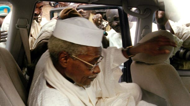 """Chad's ex-dictator Hissene Habre leaves Dakar's courthouse escorted by prison guards, November 25, 2005. Habre, detained by Senegal on Sunday in the first step towards a trial for war crimes, is known as """"Africa's Pinochet"""" for his eight-year rule over Chad which began and ended in violence."""