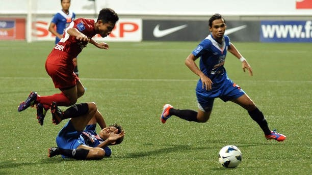 Singapore's LionsXII player Nazrul Nazari (L) leaps over KL Felda United player Mohd Akmal at the Jalan Besar Stadium during the Malaysian Super League in Singapore on July, 2 2013. The LionsXII clinched the Malaysian Super League title Tuesday with a clinical 4-0 win over minnows Felda United, rekindling the city-state's glory days in the competition after a nearly two-decade absence.