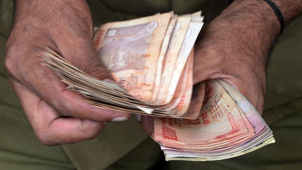 """A man counts currency notes in Mumbai on June 20, 2013. Indian companies will be """"severely"""" hit by the rupee's plunge to record lows due to their hefty foreign debts, the country's top credit ratings agency Crisil Research warned Wednesday."""