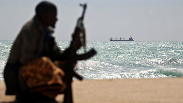 A Somali pirate stands along the coastline of Hobyo on January 7, 2010, where a Greek cargo ship is anchored offshore. The Malaysian-flagged MV Albedo container ship, seized by Somali pirates in November 2010, sank last week in rough seas a short distance offshore from the pirate-held town of Hobyo, but at least three, if not all, of the 15-man crew are alive, their families said Saturday.