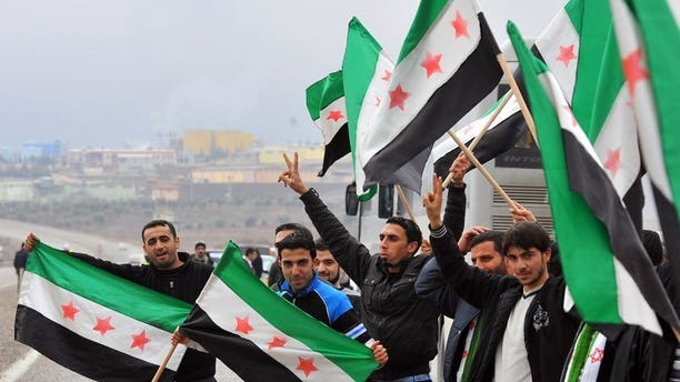Activists, including some artists, wave a Syrian flag against president Bashar al-Assad during rally on January 12, 2012, in Kilis. The wife of acclaimed Syrian artist Youssef Abdelke, whose works are displayed in museums around the world, appealed for his release on Saturday, after his arrest by regime security forces.