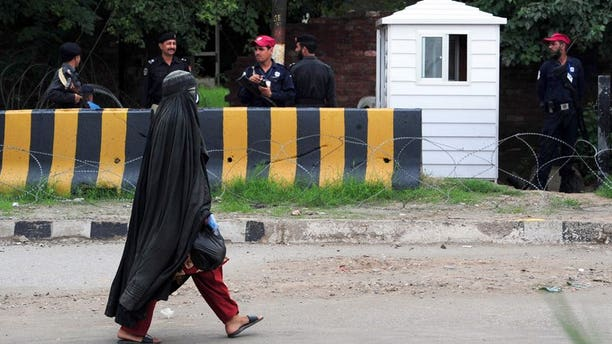 A veiled woman walks past Pakistani security personnel in Peshawar on September 17, 2012. A new cartoon superhero disguised in a flowing black burka is set to debut on Pakistani television next month in an animated series which follows her battle for girls' education in Pakistan.