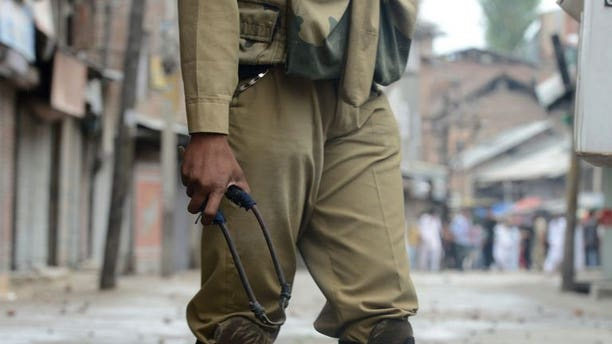 An Indian policeman holds a slingshot during clashes in downtown Srinagar on August 2, 2013. The Indian army said Friday it had killed 12 suspected militants in Kashmir in a forested area along the de facto border that divides the territory between India and Pakistan.