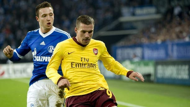 Arsenal's German striker Lukas Podolski (R) escapes from Schalke 04 midfielder Marco Hoeger during the Champions League group B match in Gelsenkirchen on November 6, 2012. Arsenal are set to loan Podolski to Bundesliga club Schalke 04 as the German international looks to get more playing time in the build-up season to next year's World Cup in Brazil.