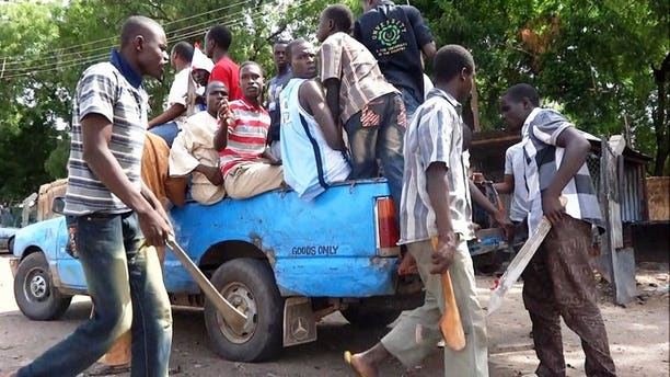 Machete and axe wielding vigilantes hop into a pick-up on July 19, 2013 for an operation to hunt down Boko Haram Islamists in Maiduguri.