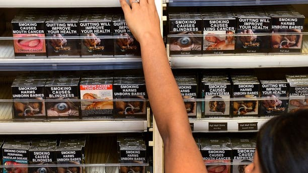 An employee adjusts packaged cigarettes which have to be sold in identical olive-brown packets bearing the same typeface and largely covered with graphic health warnings, in Sydney on December 1, 2012. Honduras on Friday raised the pressure on Australia over its landmark plain packaging rules for tobacco by launching a full-blown dispute at the World Trade Organization, the global body said.
