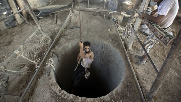 A Palestinian man is lowered into a smuggling tunnel beneath the Gaza-Egypt border, in the southern Gaza Strip, on September 11, 2013. Gaza rulers Hamas and residents of the Palestinian territory fear Egypt's destruction of tunnels used to smuggle goods across the border is part of a plan to tighten a blockade of the Strip.