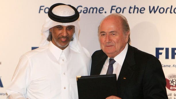 FIFA president Sepp Blatter (R) and Qatar Football Association (QFA) president, Sheikh Hamad bin Khalifa bin Ahmed al-Thani, pose with documents after officially appointing Qatar as the host of the 2022 FIFA World Cup during a function in Doha on December 16, 2010.