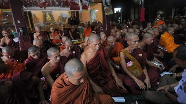 "Myanmar Buddhist monks pray during a gathering to mark the sixth anniversary of ""Saffron Revolution"" at a monastery in Yangon on September 18, 2013."