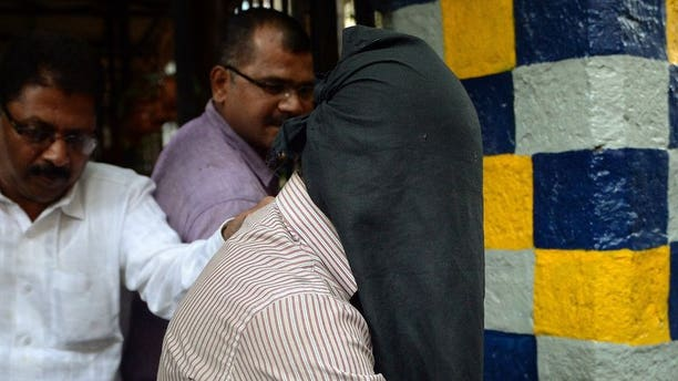 Indian police officials escort a suspect in the gang-rape of a female photographer from a crime branch unit station in Mumbai on August 26, 2013. Four men were formally charged Thursday in a Mumbai court over the gang rape of a young photographer in the city -- a case that reignited anger about women's safety across India.