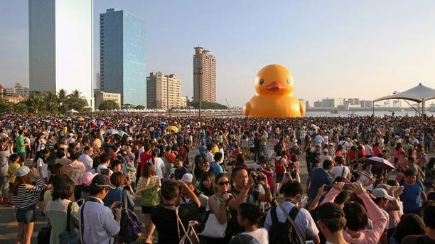 Local residents gather to see Dutch artist Florentijn Hofman's yellow rubber duck at a harbour in the Taiwanese city of Kaohsiung on September 19, 2013. A Dutch artist's now-famous giant yellow duck found a new temporary home Thursday, this time in Taiwan, but an approaching typhoon could ruffle the inflatable's feathers.