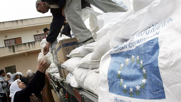 A Palestinian woman receives foodstuffs donated by the European Union through the World Food Programme and distributed by the United Nations Relief and Works Agency (UNRWA) in the West Bank city of Jenin, December 16, 2007.