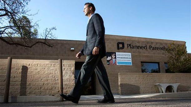 In this Jan. 23 photo, Bryan Howard, CEO of Planned Parenthood Arizona, walks in front of a Planned Parenthood facility in Tucson, Ariz.