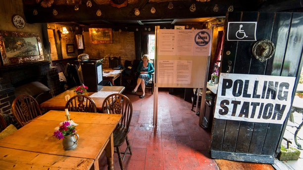 The scene inside the White Horse Inn in Priors Dean, Hampshire, England also known as the 'Pub with no name' which has been made a polling station for the EU referendum Thursday June 23, 2016. Voters in Britain are deciding Thursday whether the country should remain in the European Union. (Andrew Matthews/PA via AP)