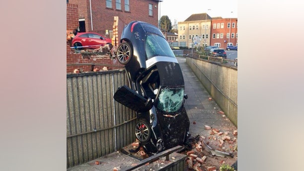 The catastrophic result of a 73 year old's Porsche colliding with a call and crashing into a pedestrian subway. See Masons story MNPORSCHE; The incident happened just after 6pm on Thursday evening (5 Apr). it is believed that the car was parked in a car park before it crashed through the wall. Several police cars and two fire engines were sent to the scene.