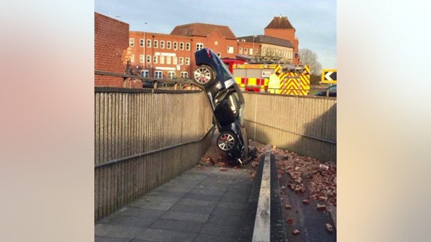 The car landed on top of a 10-foot-tall barrier wall and tipped onto its nose.