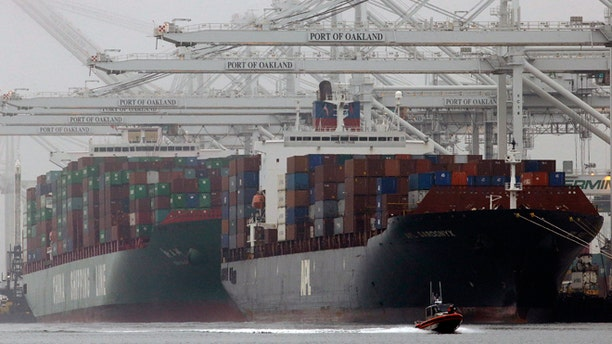 Oct. 23, 2013: In this file photo, container ships wait to be off-loaded at the Port of Oakland in Oakland, Calif. The West Coast ports that are Americas gateway for hundreds of billions of dollars of trade with Asia and beyond are no stranger to labor unrest and even violence. Now, the contract that covers nearly 20,000 dockworkers is set to expire, and businesses that trade in everything from apples to iPhones are worried about disruptions as the summer cargo crush begins.